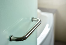 Glass Door Handle Of A Glass Partition Shower Unit. Bathroom Glass Door Detail With Bath Tub In The Background. Selective Focus And Soft Light Effect Added.