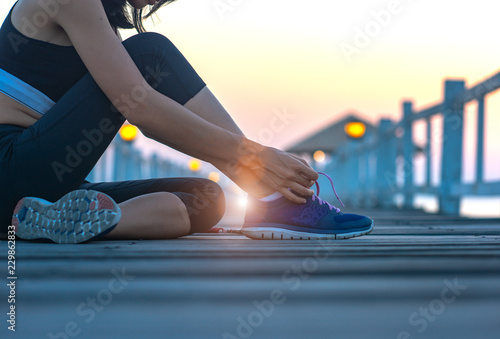 Obraz woman sitting on the wooden pier lace tie of the shoe, excercise running and jogging in daily morning healthy lady morning light - fototapety do salonu