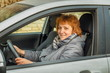A middle-aged woman is driving a car.