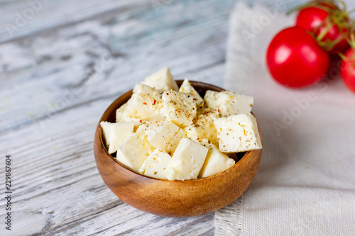 Feta cheese cubes in wooden plate on white wood