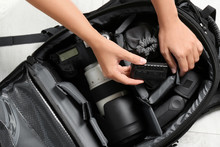 Woman Putting Professional Photographer's Equipment Into Backpack On Floor, Top View