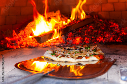 Man is placing a freshly prepared pizza into an outdoor bread oven - closeup picture - Pictures taken during a bread and pizza making workshop with many people from all ages and generations