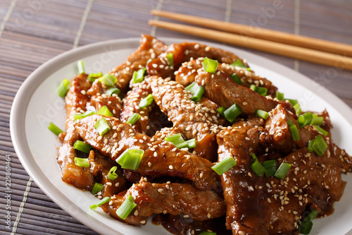 Popular Asian beef in teriyaki sauce with sesame close-up on a plate. horizontal