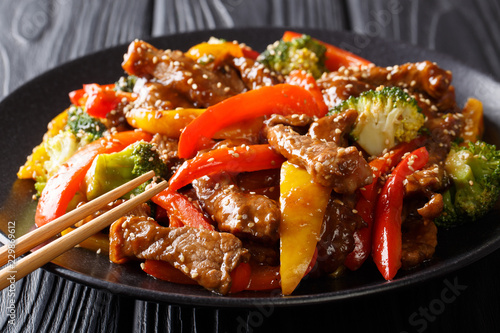 Fotobehang Schaaldieren Stir-fried teriyaki beef with red and yellow bell pepper, broccoli and sesame seeds close-up on the table. horizontal