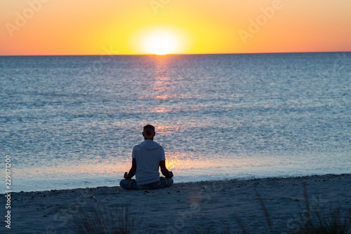 Man sits on the beach next to surf line, practicing yoga