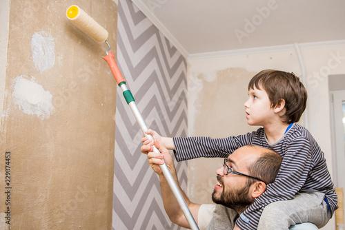 Obraz father and child paint walls, glue wallpaper, apply glue. - fototapety do salonu