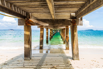 FototapetaBeautiful picture splashing sea wave under the old concrete and wooden bridge.