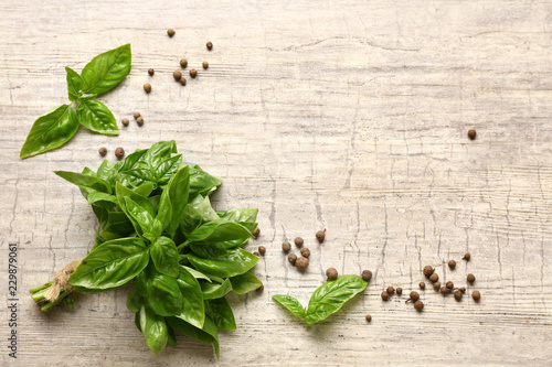 Fototapeta Fresh aromatic basil with spices on light background obraz