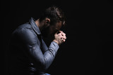Religious young man praying to God on black background
