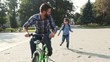 Happy good-looking Caucasian man with beard riding a bicycle in park. Nice son wearing helmet running after daddy. Game in park. Summertime. Outdoors.