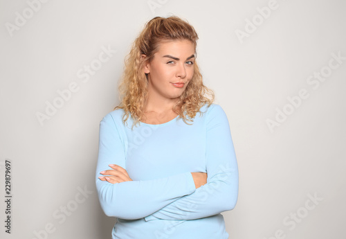 Fototapety, obrazy: Portrait of suspicious young woman on light background