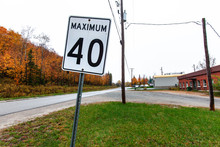 Maximum 40 Km Per Hour White Road Sign - Picture Taken In Quebec, Canada, While Autumn Colors Were Very Present. Perspective From The Side Of The Road