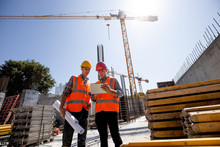Civil Architect  And Construction Manager  Dressed  In Orange Work Vests And  Helmets Discuss  A Building Project On The Mobile Tablet On The Open Building Site Next To The Crane