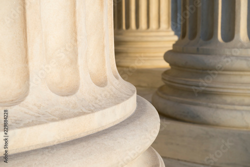 Fototapeta Lower detail of classical fluted columns in a colonnade in white marble lit by soft golden sunlight obraz