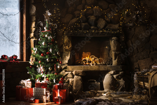 Photo Christmas decorated fireplace and gifts in cozy chalet