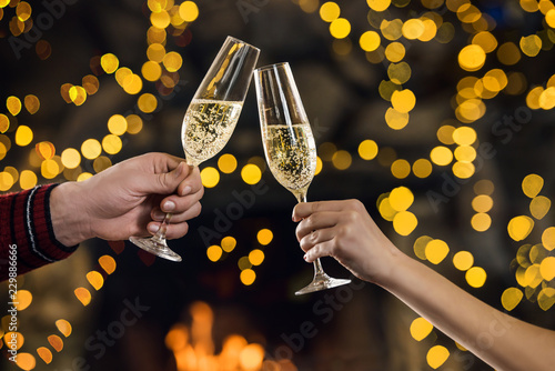 Couple clink champagne glasses at night on bright holiday
