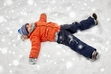 Childhood, Leisure And Season Concept - Happy Little Boy In Winter Clothes Making Snow Angels Outdoors