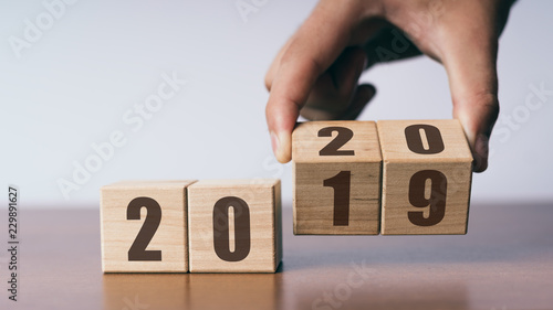 New year 2019 change to 2020 concept, hand change wooden cubes