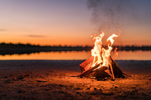 Small Campfire With Gentle Flames Beside A Lake During A Glowing Sunset. Western Australia, Australia.