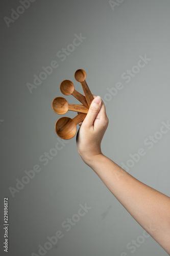 Fotografia, Obraz  measure spoon table spoon tea spoon in hand grey background