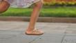 Little Caucasian girl in elegant romantic dress running dawn the street. Legs of naughty kid wearing wonderful pink sandales. Summertime.