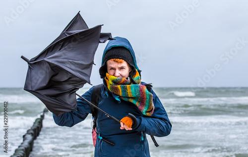 strong wind destroys a woman's umbrella during a beach walk Fototapeta