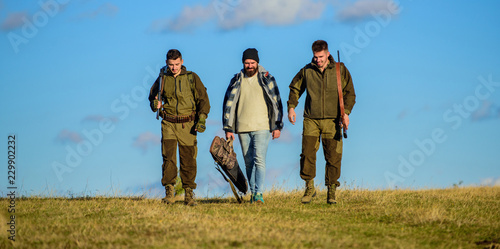 Foto op Canvas Jacht Hunters with guns walk sunny fall day. Brutal hobby. Group men hunters or gamekeepers nature background blue sky. Guys gathered for hunting. Men carry hunting rifles. Hunting as hobby and leisure