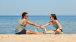 fitness, sport and lifestyle concept - smiling couple stretching legs on beach before training