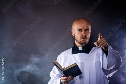 Fotografie, Obraz  Catholic priest in white surplice and black shirt with cleric collar reading bib