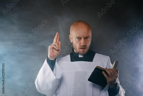 Obraz na plátně Catholic priest in white surplice and black shirt with cleric collar reading bib