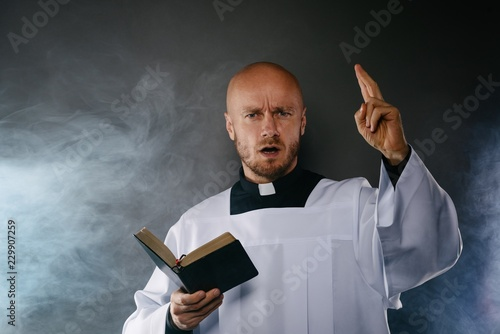 Fotografie, Obraz  Catholic priest in white surplice and black shirt with cleric collar reading bib
