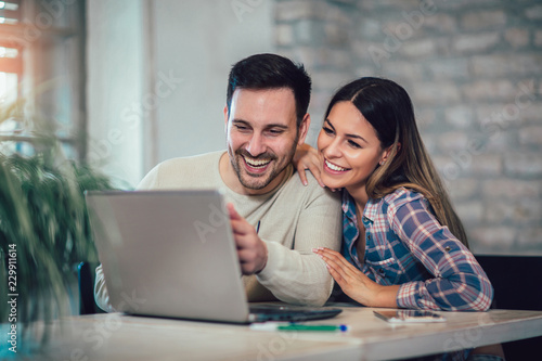 Plakat Young Couple Using Laptop On Desk At Home