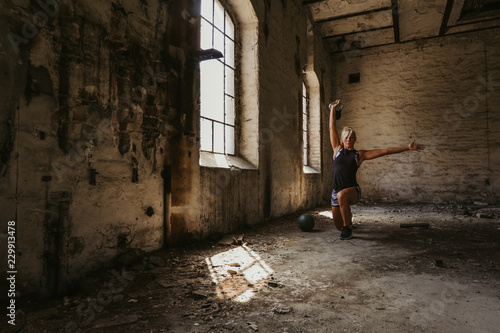 Athletic woman doing kettlebell lunge press in an old building