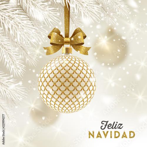 Fototapeta Feliz navidad - Christmas greetings in Spanish - patterned golden bauble with glitter gold bow hanging on a christmas tree. Vector illustration. obraz na płótnie