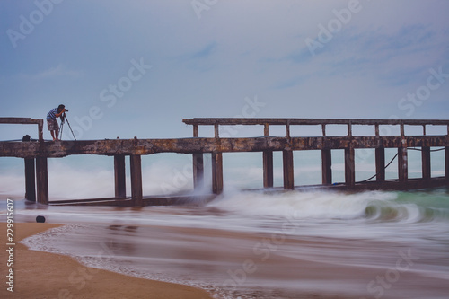 man taking a photograph of beach pier in rain storming day