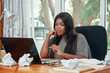 Stylish modern black woman watching laptop at table with papers sitting alone in office