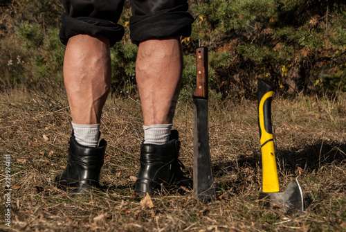 Strong legs of a man, standing near machete, stuck in the ground. Beautiful masculine legs with calf muscles, rear view. Concept - active lifestyle.