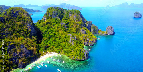 Exotic Beach Cove With Catamaran Style Boats On Rocky Tropical Island - El Nido, Palawan, Philippines - Aerial View
