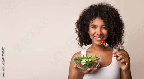 Fotografía  African-american woman eating vegetable salad over light background