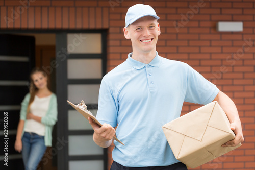 Fotografie, Obraz  Smiling courier in uniform holding package and delivering it to recipient
