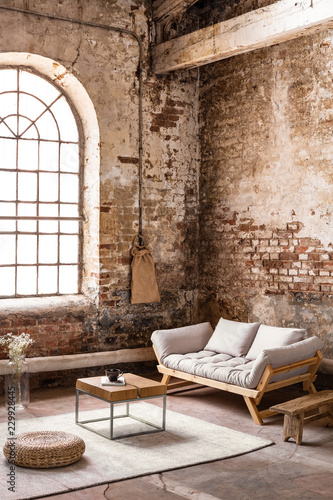 Pouf and table on rug in front of wooden sofa in spacious loft interior with window Canvas Print
