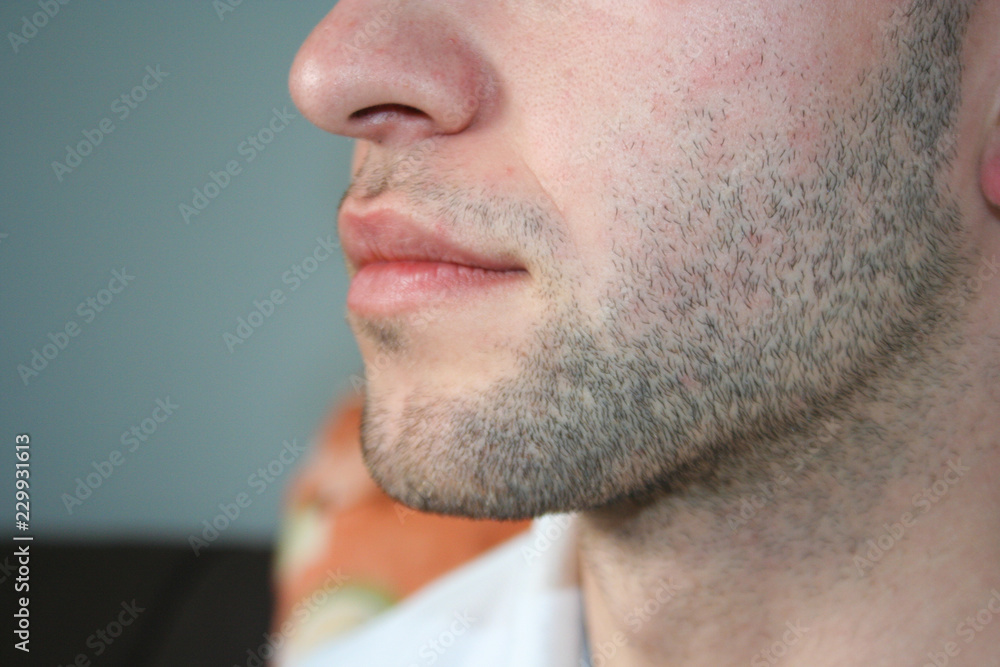 Fototapeta A man's face with a slight beard. A few days beard on the guy's chin. Macro picture taken from the profile.