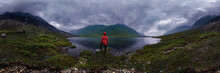 Man Stands By Lake In Red Jacket In Cloudy Weather. Cylindrical Panorama 360vr
