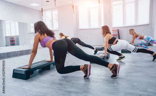 Fotografie, Obraz  Young fitness women using step platform at the gym