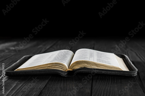 the open book Bible on a black wooden background