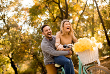 Active Young Couple Enjoying Riding Bicycle In Golden Autumn Park