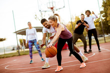 Group Of Multiracial Young People   Playing Basketball Outdoors