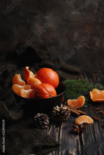 Raw organic Christmas tangerines in a black bowl with Christmas decoration on a wooden table. Dark and moody. Close up. Copy space