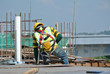 Construction workers wearing safety harness belt at other safety gear during working at the construction site area.