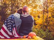 Happy Married Couple Holding The US Flag Against The Background Of Yellow Trees And The Setting Sun. Happy Relationship Concept